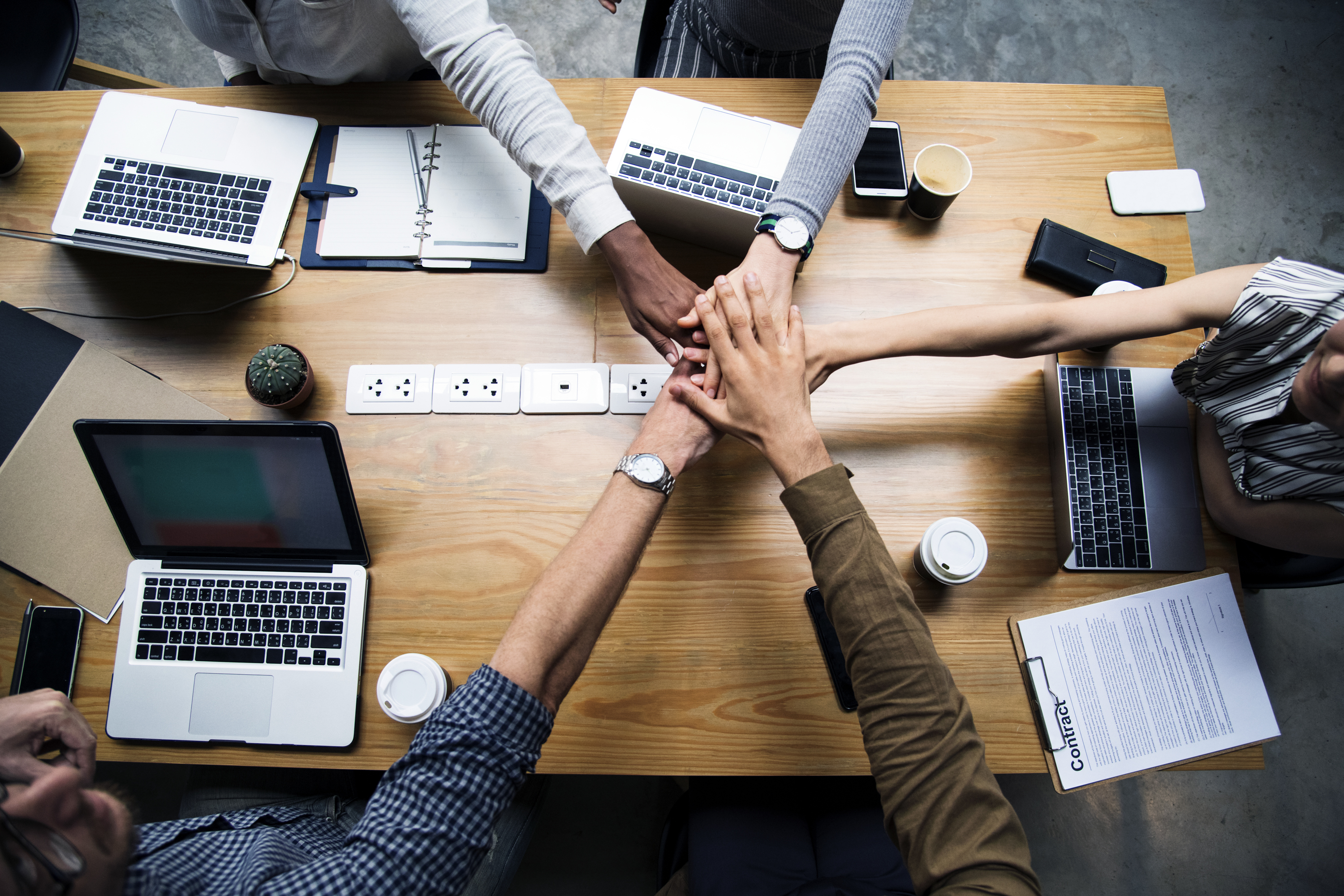 Team of business people stacking hands
